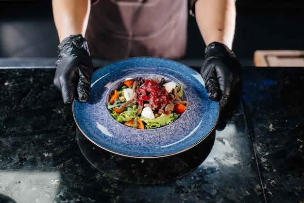 Uno chef professionista serve un'insalata preparata al momento di pomodori e verdure di vitello con salsa in un primo piano di un ristorante gourmet