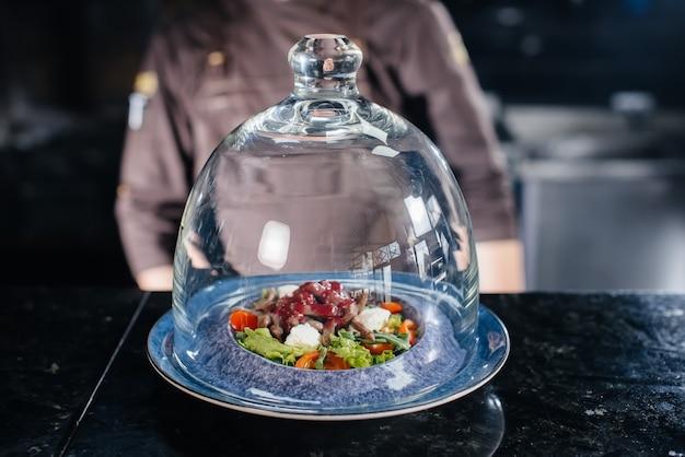 Uno chef professionista serve un'insalata preparata al momento di pomodori e verdure di vitello con salsa in un ristorante raffinato sotto una cupola di vetro