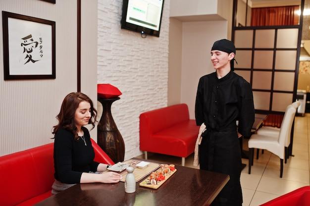 L'abbigliamento da chef professionale in nero offre sushi e panini per cliente donna in un ristorante di cibo tradizionale giapponese.