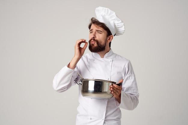 Chef professionista con una casseruola in mano che prova il lavoro di cottura del cibo