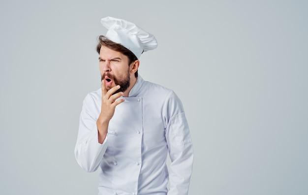 Chef professionisti in uniforme gesticolano con le mani su uno sfondo chiaro, vista frontale. foto di alta qualità