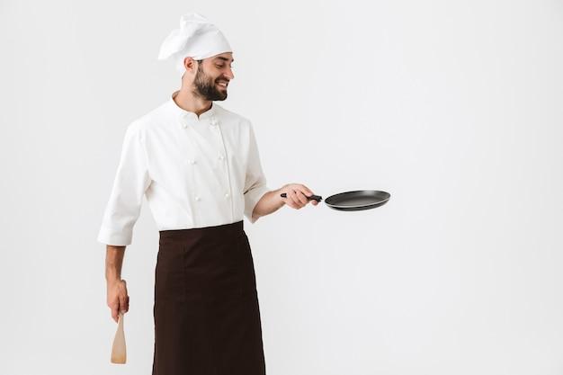 Capo professionista in uniforme da cuoco che tiene in mano una spatola da cucina in legno e una padella isolata su un muro bianco