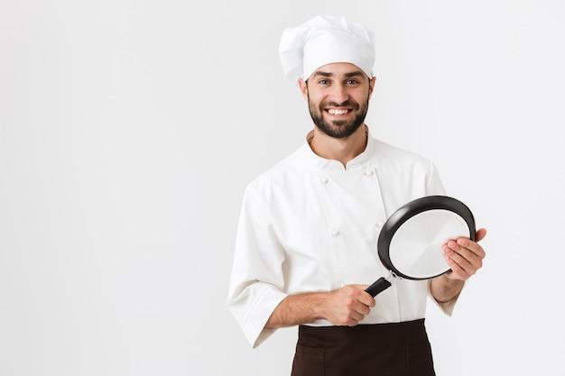 Capo professionista in uniforme da cuoco sorridente e tenendo la padella isolata su un muro bianco