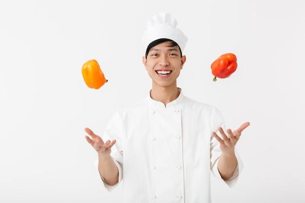 Capo uomo professionista cinese in uniforme bianca da cuoco sorridendo alla telecamera mentre si tiene in mano carta dolce verdure isolate su muro bianco