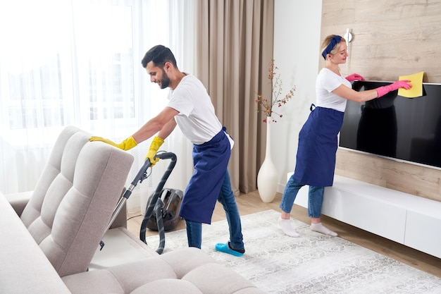 Detergenti professionisti in divisa blu che lavano il pavimento e puliscono la polvere dai mobili nel soggiorno dell'appartamento. concetto di servizio di pulizia
