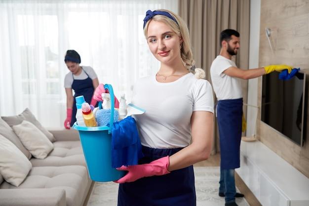 Il team di servizio di pulizia professionale pulisce il soggiorno in un appartamento moderno