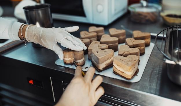 Pasticciere professionista che lavora alla realizzazione e alla decorazione di deliziosi dolci.