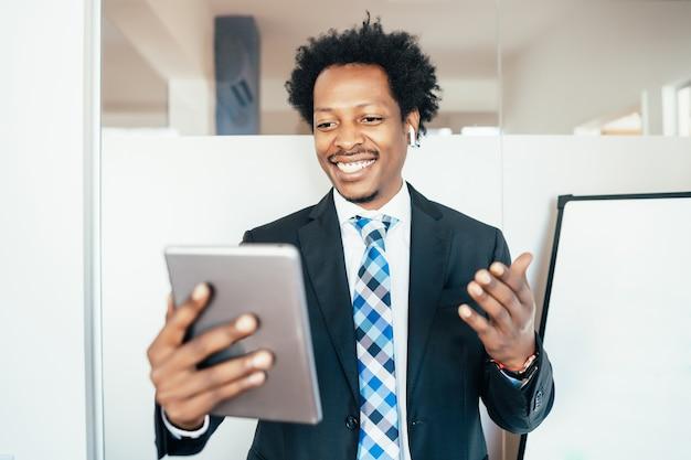 Uomo d'affari professionale e fiducioso in una riunione virtuale in videochiamata con tavoletta digitale in ufficio