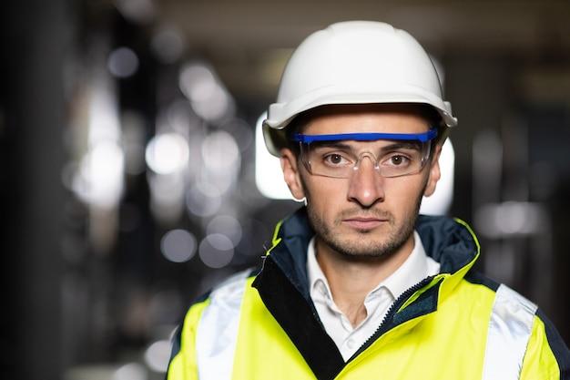 Ingegnere serio e fiducioso professionista che guarda la telecamera indossando uniformi di sicurezza e occhiali di protezione