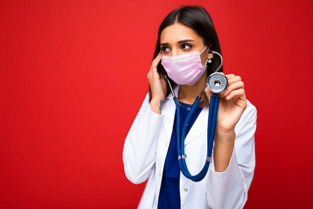 Professionista fiducioso giovane donna europea brunnet medico in mascherina medica e camice bianco, stetoscopio
