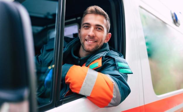 Medico professionale e fiducioso del giovane con l'ambulanza