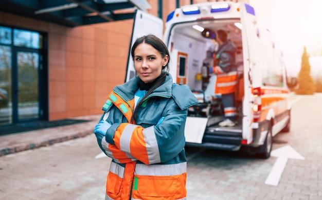 Medico professionale e fiducioso della giovane donna con l'ambulanza
