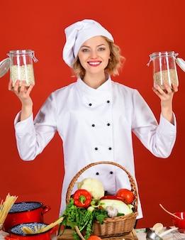 Cuoco professionista in uniforme bianca con barattoli di cereali. cucina e preparazione dei cibi.