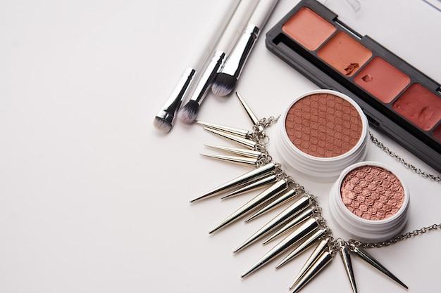 Cosmetici professionali e accessori alla moda su un tavolo grigio