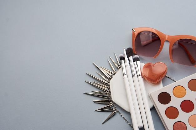 Occhiali alla moda cosmetici professionali su un supporto su uno sfondo grigio e pennelli per il trucco
