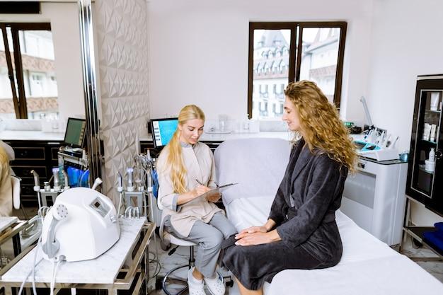 Cosmetologo professionista. medico femminile che parla con sua giovane donna del cliente mentre lavorando nella clinica di bellezza, prendendo appunti sul tipo e sul problema di pelle.
