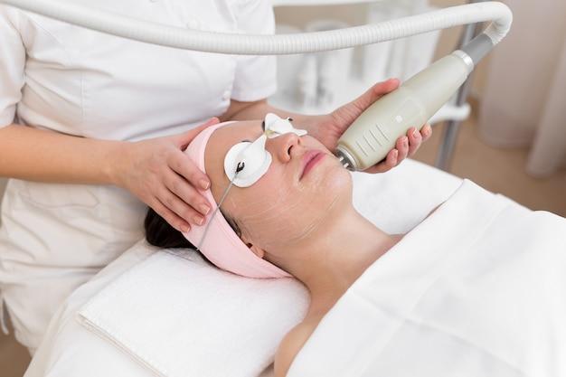 Cosmetologo professionista sta effettuando un trattamento della pelle di ringiovanimento della cavitazione. la giovane donna sta mentendo e sta rilassando. sollevamento delle onde radio