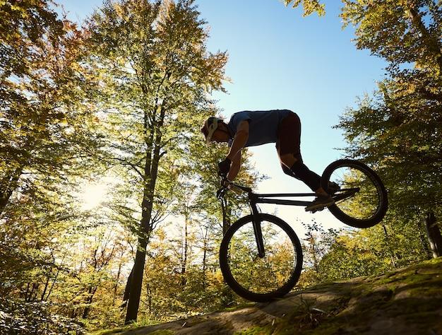 Ciclista professionista in equilibrio sulla bicicletta di prova al tramonto