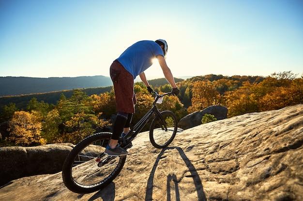 Bilanciamento del ciclista professionista sulla bicicletta di prova al tramonto