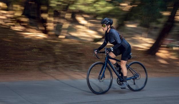 Ciclista professionista ad alta velocità su strada con la sua bici da pista triathlon concept
