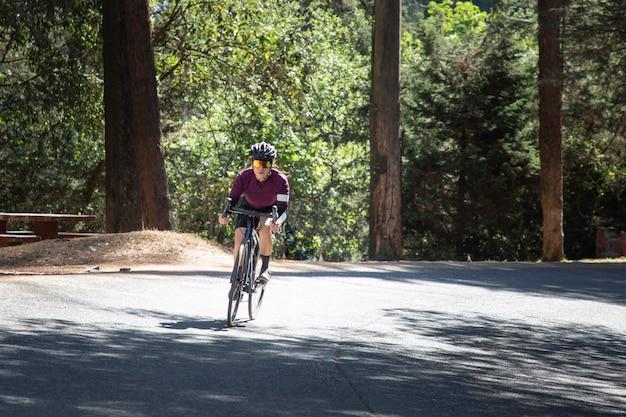 Donna ciclista professionista che accelera su una strada nel mezzo della foresta concetto di triathlon