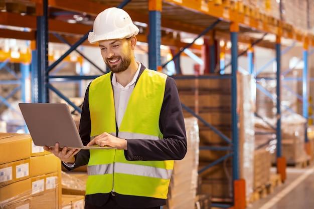 Responsabile delle consegne professionale che utilizza il laptop per il suo lavoro mentre si occupa della distribuzione di merci su larga scala