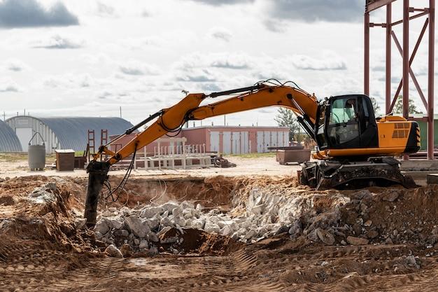 Demolizione professionale di strutture in cemento armato mediante martello idraulico industriale con escavatore. barre di accessori metallici. relitti e briciole di cemento.