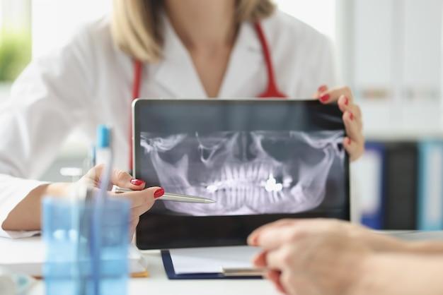 Il dentista professionista mostra ai pazienti i raggi x delle mascelle e dei denti utilizzando un dispositivo tablet digitale medico