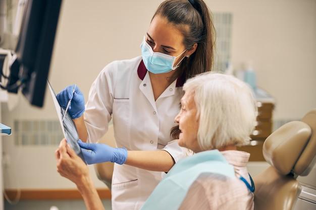 Dentista professionista che parla con la sua paziente anziana che la sostiene prima di iniziare le procedure dentistiche presso la clinica