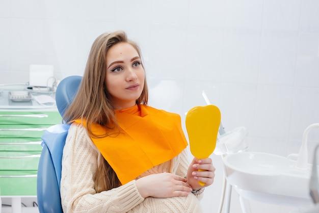 Un dentista professionista tratta ed esamina la cavità orale di una ragazza incinta in un moderno studio dentistico