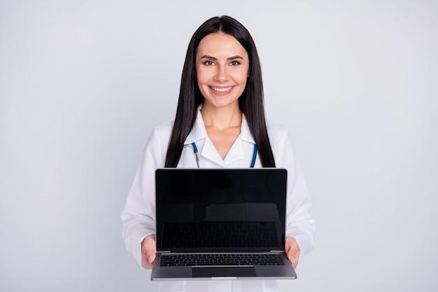 Signora professionale doc che mostra lo schermo del laptop su sfondo grigio