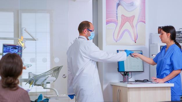 Medico professionista che chiede una radiografia dentale prima di esaminare il paziente mentre le persone aspettano nell'area della reception della moderna clinica stomatologica. infermiera odontoiatrica digitando sul computer per fissare appuntamenti.