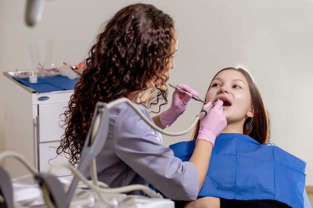 Il dentista professionista del medico esamina e tratta i denti rovinati con l'uso di strumenti dentali speciali, attrezzature mediche