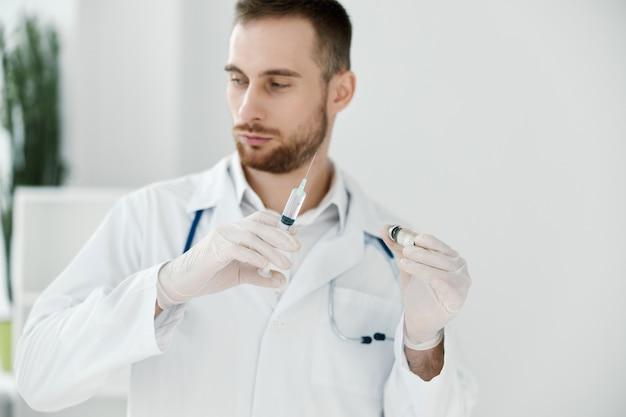 Un medico professionista in camice medico è affettuoso e con guanti protettivi tiene una fiala con un vaccino