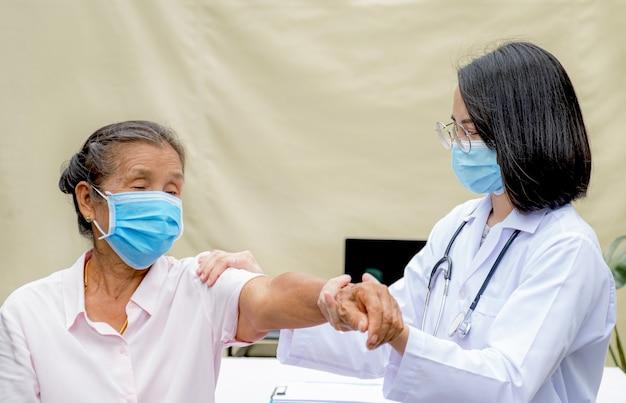 Una terapia fisica del medico professionista sta facendo la terapia della mano ai pazienti anziani nell'ospedale.