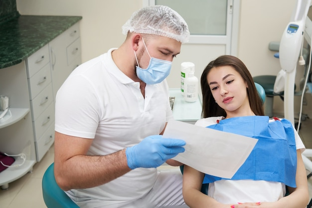Il medico professionista mostra l'immagine del paziente dei denti nel suo studio dentistico medico.