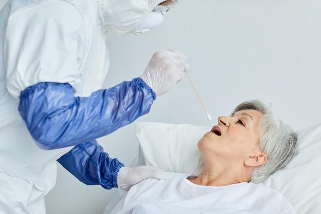 Medico professionista che indossa l'uniforme protettiva che prende il tampone della donna senior per il test antivirus pericoloso utilizzando il bastone