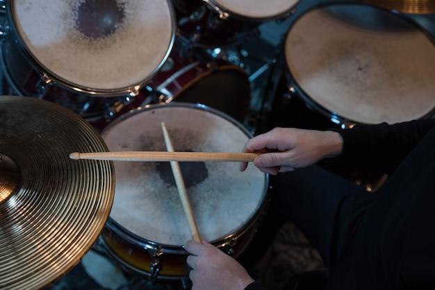 Primo piano professionale della batteria. uomo batterista con bacchette che suona batteria e piatti, al concerto rock di musica dal vivo o in studio di registrazione