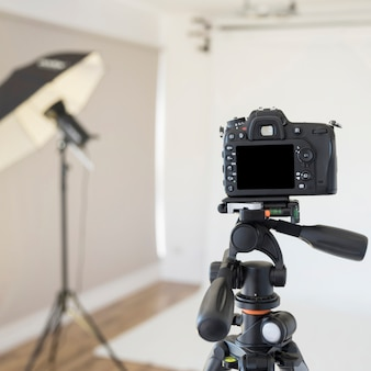 Fotocamera digitale professionale dslr su treppiede in studio fotografico