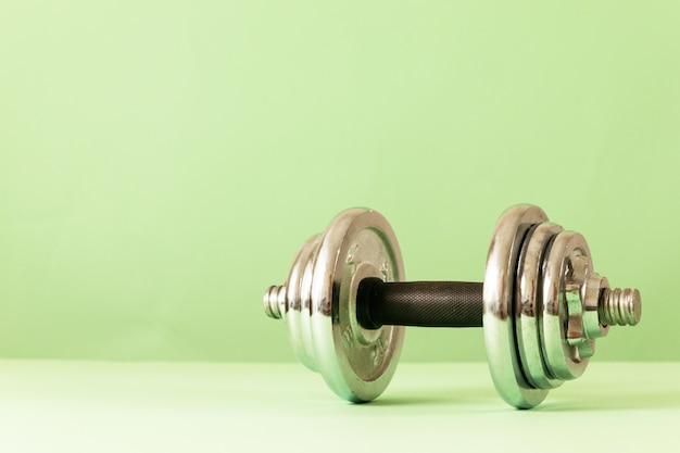 Dumbbell professionale su uno sfondo verde, concetto di preparazione per attrezzature sportive fitness