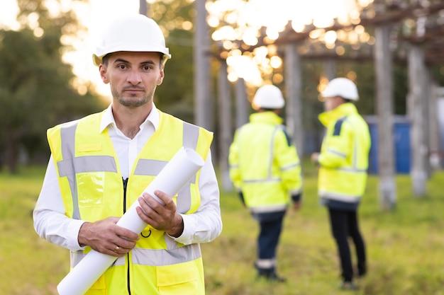 Ingegnere professionista dell'industria elettrica che sorride e guarda i lavoratori della telecamera che indossano la sicurezza
