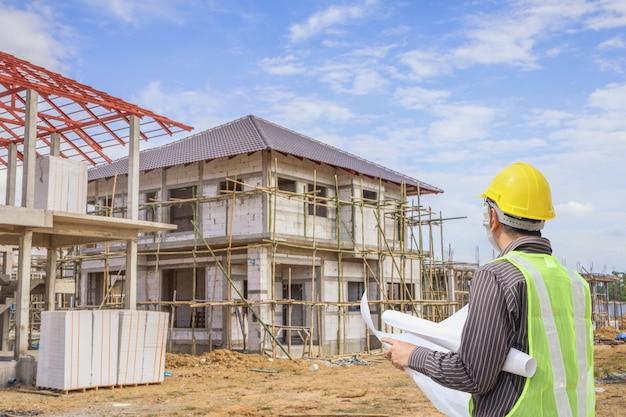 Operaio professionista architetto ingegnere con casco protettivo e carta cianografie al fondo del cantiere di costruzione di casa