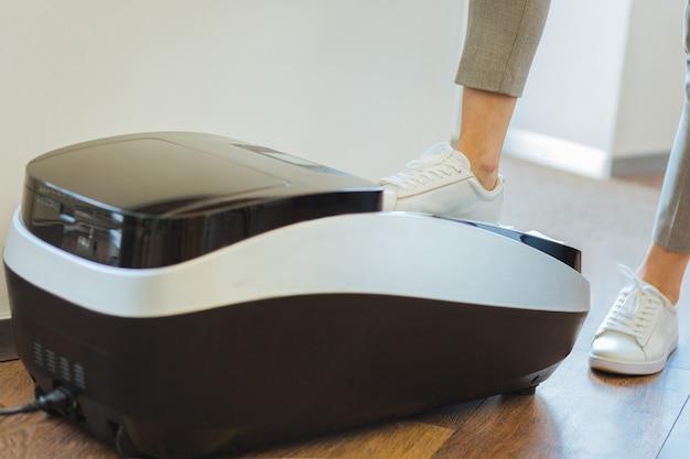 Attrezzatura professionale. primo piano di un dispositivo professionale in piedi sul pavimento con una bella donna in forma che mette la gamba su di esso