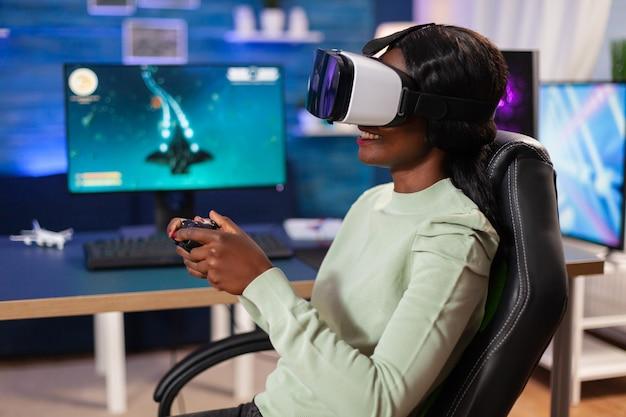 Lettore di esport professionale con auricolare vr tramite joystick wireless. campionato di gioco sparatutto spaziale virtuale nel cyberspazio, giocatore di esport che si esibisce su pc durante il torneo di gioco.