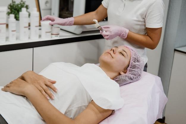 L'estetista professionista applica la maschera facciale al viso dei clienti nel centro di bellezza spa giovane donna