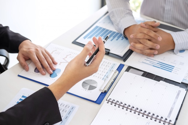 Manager esecutivo professionale, socio commerciale che discute il piano di marketing di idee e progetto di presentazione dell'investimento alla riunione e che analizza sui dati del documento, sul concetto finanziario e di investimento