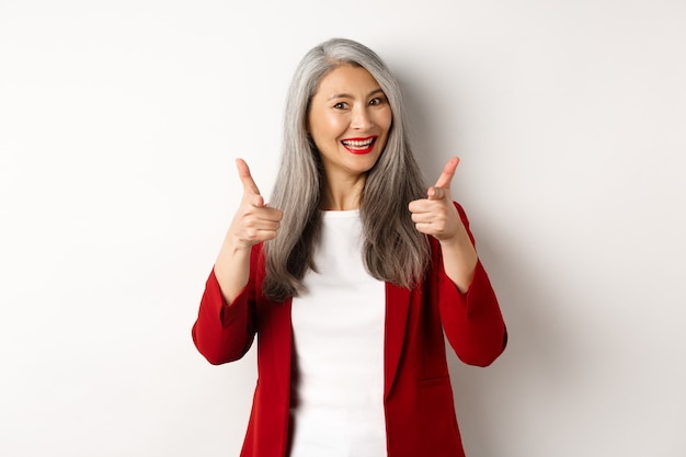 Datore di lavoro femminile professionale in blazer rosso alla moda e trucco, puntando il dito verso la telecamera e sorridendo, lodando qualcosa, hai bisogno di te, in piedi su sfondo bianco.
