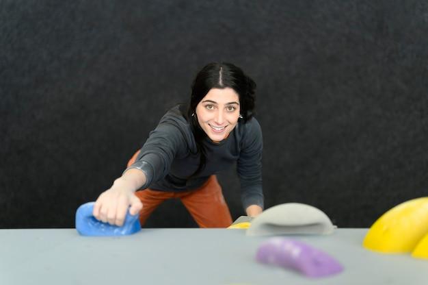 Scalatore professionista di fitness femminile in palestra boulder