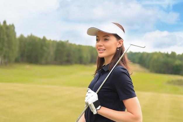 Golfista femminile professionista che tiene mazza da golf sul campo e distoglie lo sguardo. giovane donna in piedi sul campo da golf in una giornata di sole.