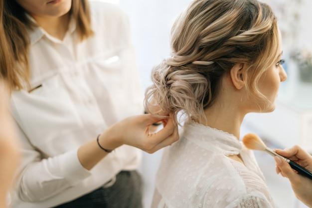 Parrucchiere femminile professionista che fa acconciatura da sposa per la sposa